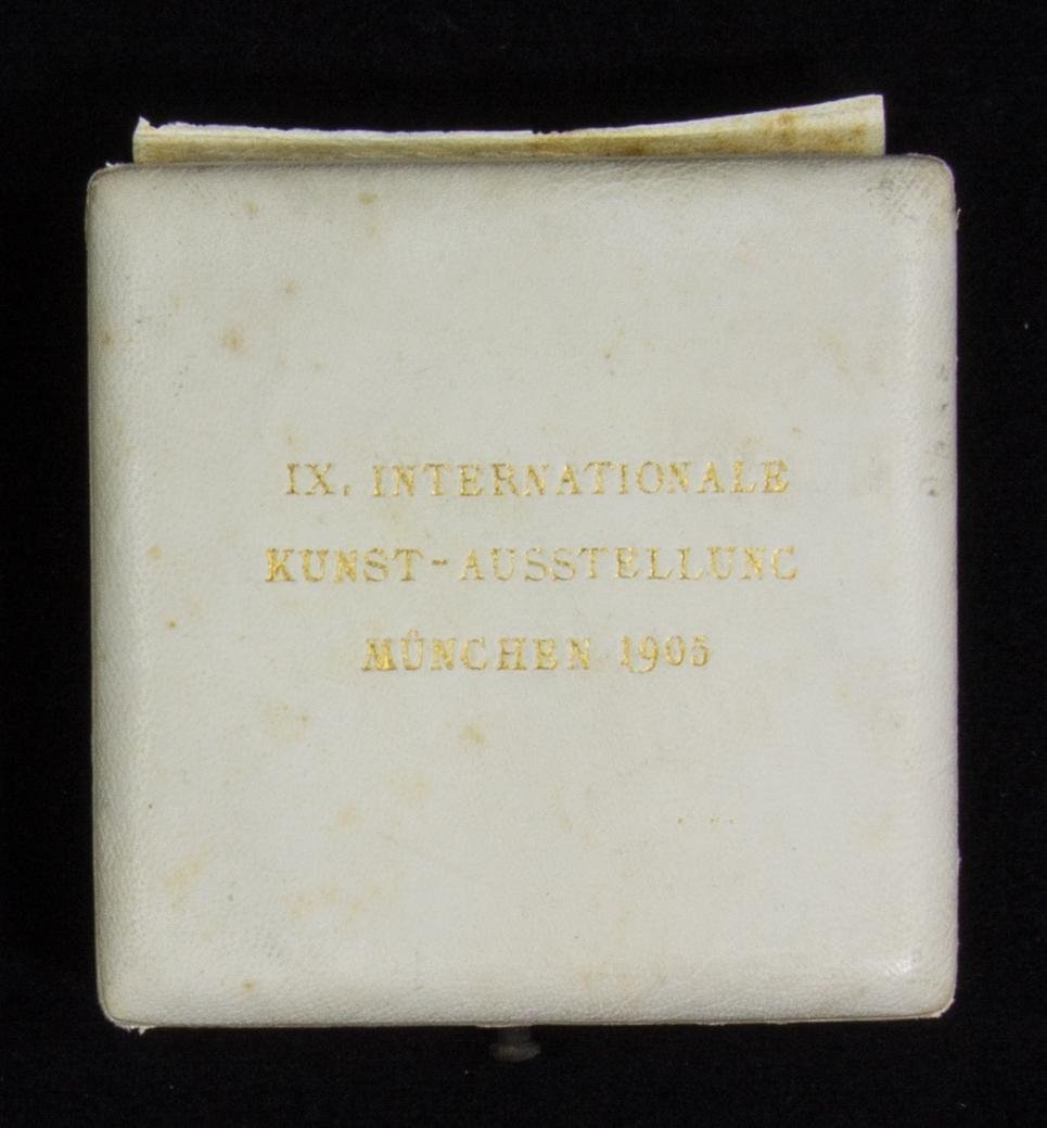 Medalj av guld med präglad text i kvadratiskt etui klätt med vitt skinn samt diplom.