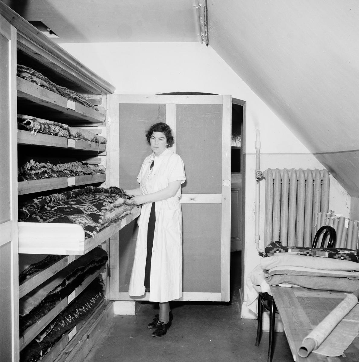 Porträtt av Elisabeth Strömberg, textilexpert på Nordiska museet som sedan övergick till Röhsska museet. Här står hon i magasin med museiföremål, textilier, förvarade i lådor.