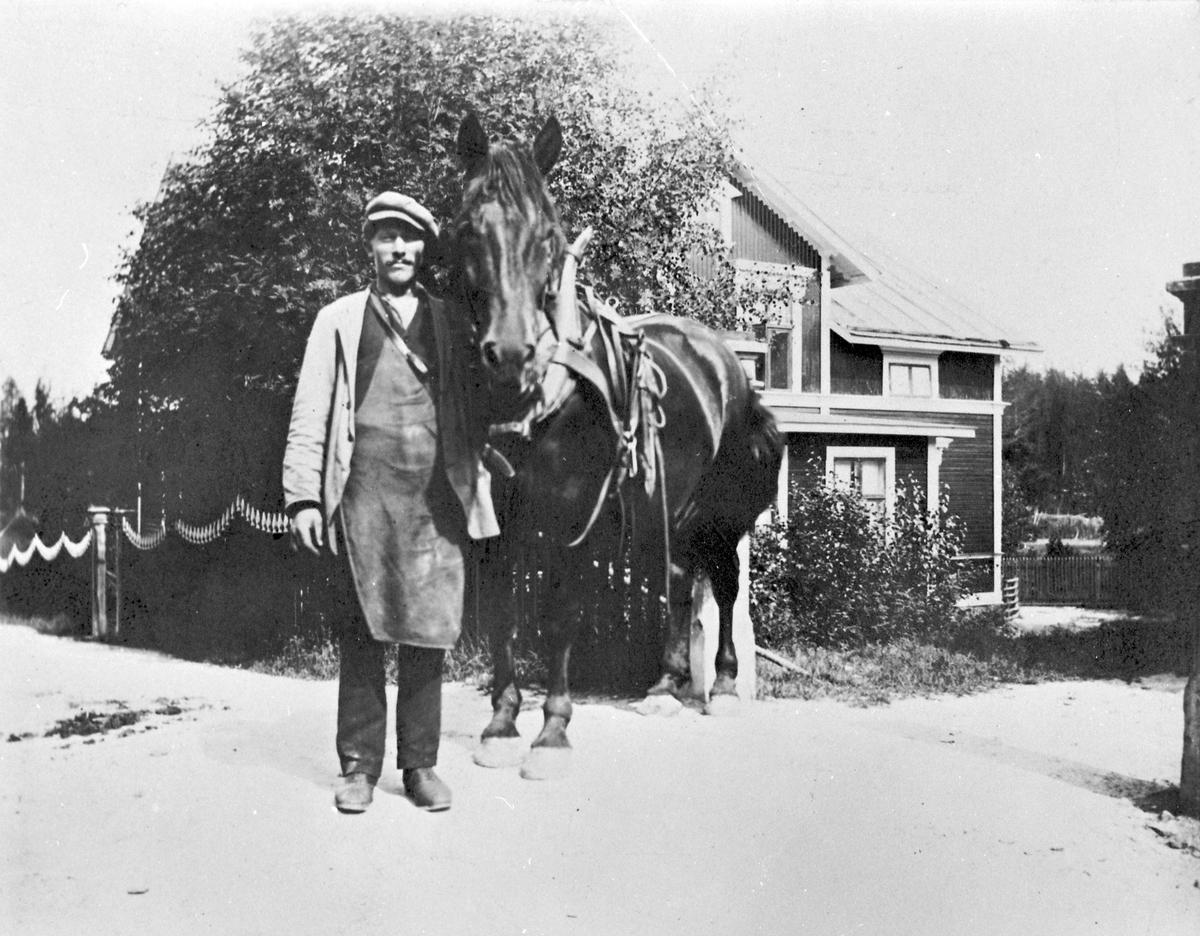 Bryggarhäst med kusken som troligen är Per Olof Sahlin (1873-1953). Han var anställd som utkörare på Wilanders bryggeri. Bakom hästen syns Brinkgården på Kvistholmen.