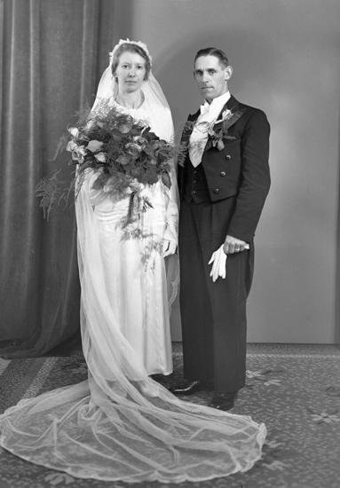 4a45013f1302 Foto av ett brudpar. Hon är klädd i lång vit brudklänning med slöja ...
