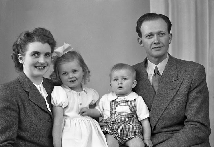 Foto av en familj med två små barn (en flicka och en pojke).Midjebild. Ateljéfoto.Trol. : Simon Göte Andersson (1915-1998), Virestad. Gift 1945 med Greta Mebel Ingeborg (1924-1998).Källa: Sveriges Dödbok 1901-2009.