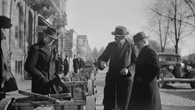 Foto av en verksamhet på Sigfridsmässan.Det syns några män som tittar på något. Till höger syns en bil.