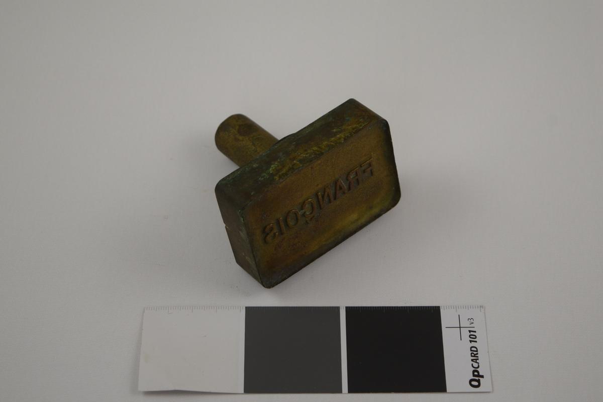 Rektangulær såpeform/stempel for produksjon av såper ved Saanums Sepefabrik i Mandal. Sannsynligvis jern med messing utenpå.  Konkav innside med relieff med motiv/tekst for trykk.