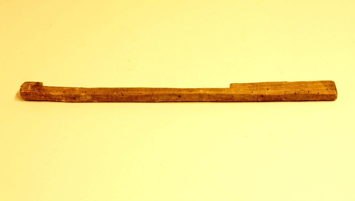 Form: Avlang pinne med utsparing for mål av hummer.