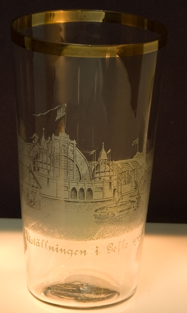 Dricksglas tillverkat för gefleutställningen 1901. Guldkant upptill. Maskinetsad dekot föreställande utställningens huvudentré och txt: Minnesutställningen i Gefle 1901.