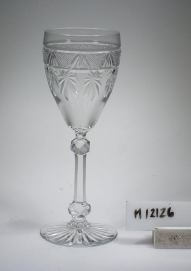 Glas (R.381). Beskrivning: Slipad dekor bestående av små skär-rutor och facetter. Två stycken slipade kulor på benet. Färg: Ofärgat klarglas. Mått: Diameter ovan avser glasets fotdiameter. Inskrivet i huvudkatalogen 1942. Funktion: Servisglas