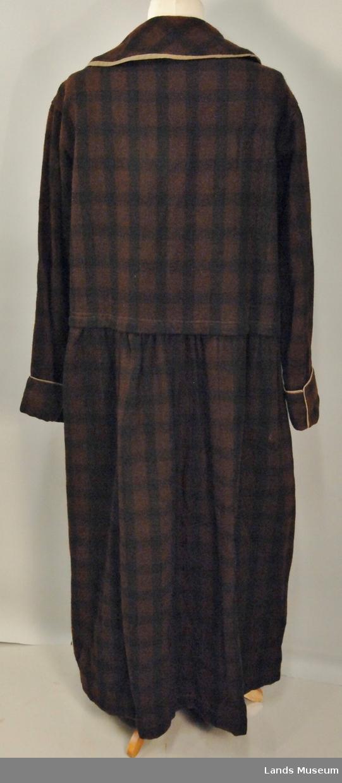 Kjolen er i rutemønster, brune på 3x3 cm, og svarte på 2x2 cm. Kjolen har 1 lomme. Krage og oppslag på ermene er pyntet med beige lerretbånd. 5 trykknapper. Skjørtet rynket på livet. Helklippet innfelling i front.