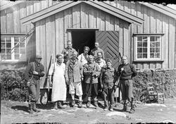 Motstandsfolk med våpen foran hytte.
