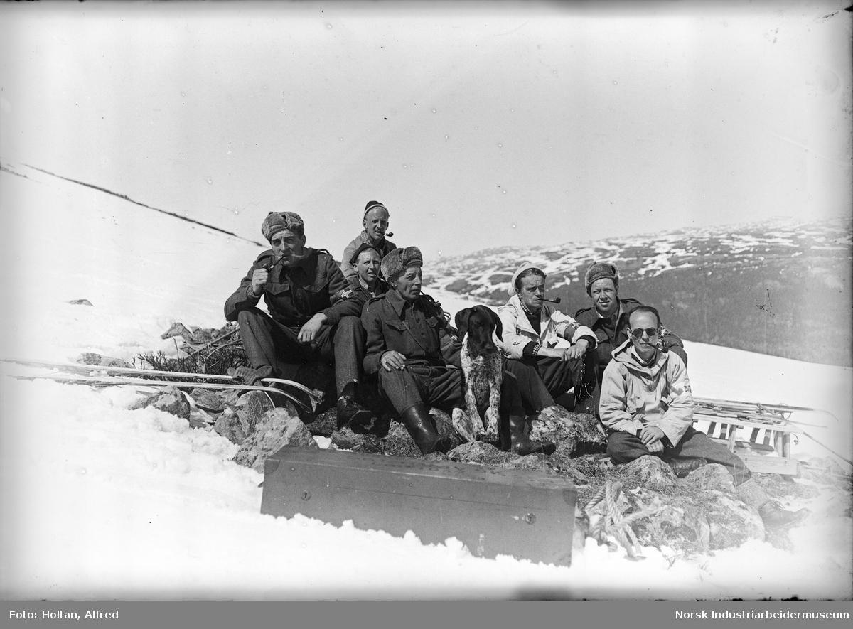 Soldater på fjellet. Selvutløser, fotografen med pipe og lys anorakk til høyre.