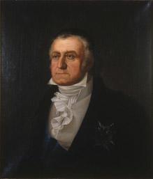 Portrett av Peder Anker. Mørk drakt, hvit vest og skjorte. Blått ordensbånd, orden festet på brystet.