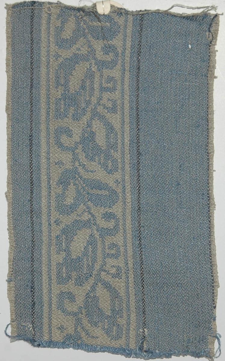 Tidigare katalogisering enl uppgift av Elisabeth Thorman kompletterad 1958 av Elisabeth Stawenow:  Möbeltyger, damast, 13 st, prover i olika färger  j) 14,5 x 24 cm. Varp av ljusgrått merc. bomullsgarn. Väft av ljust blågrått lingarn. Enstaka smala ränder av mörkare blått lingarn. Nr 50e.