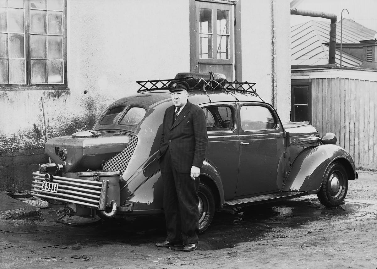 En chaufför vid en1937 Plymouth P4 med gengasaggregat. Maskincarli AB. Stockholm.