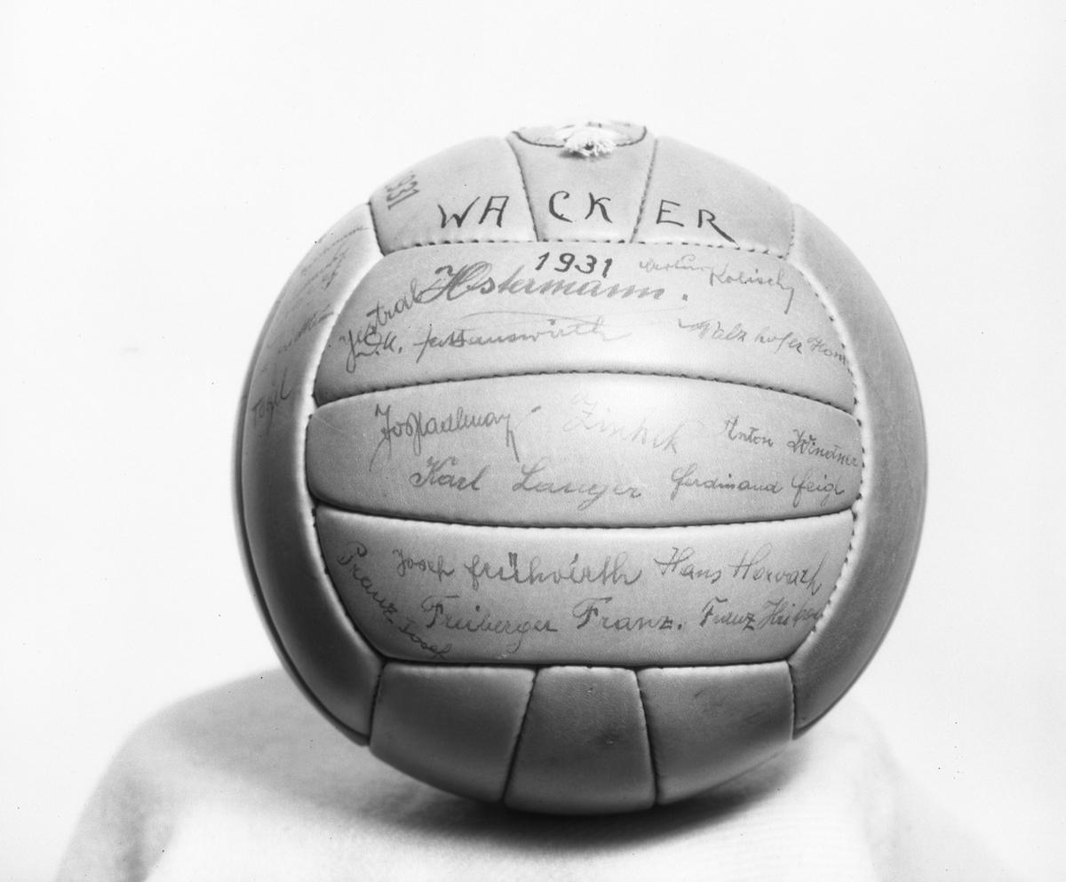 """Malmbergs startades 1905 av Elof Malmberg. Blev en av Sveriges ledande producenter av artiklar för idrott, jakt, fiske, skytte och friluftsliv. På bilden en fotboll med texten """"Wacker, 1931"""" och autografer."""