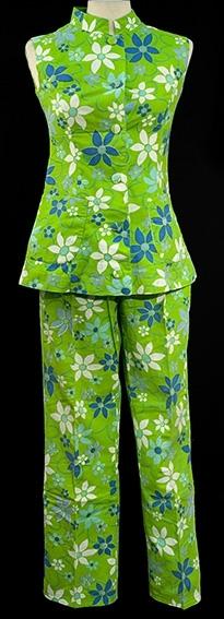 Sommerdress best. av bukse og vest. Grønn med blått og hvitt blomstermønster. Bukse med rette ben, glidelås i siden og linning med knapp. Vest med smal krage, to utenpåsydde lommer og kineserlinning.