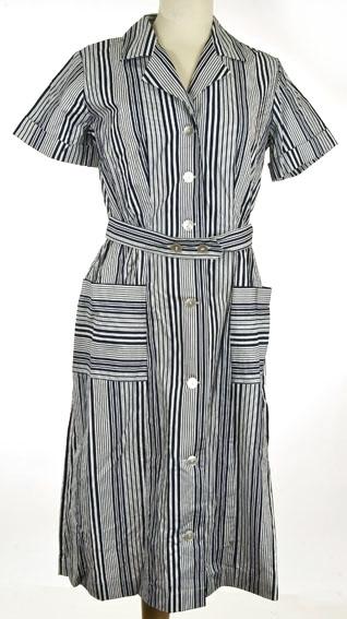 Forklekjole med skjorte fasong. Knelang med korte ermer, helskåret foran, todelt ryggstykke og strikk i livet. Blått- og hvitstripet mønster.
