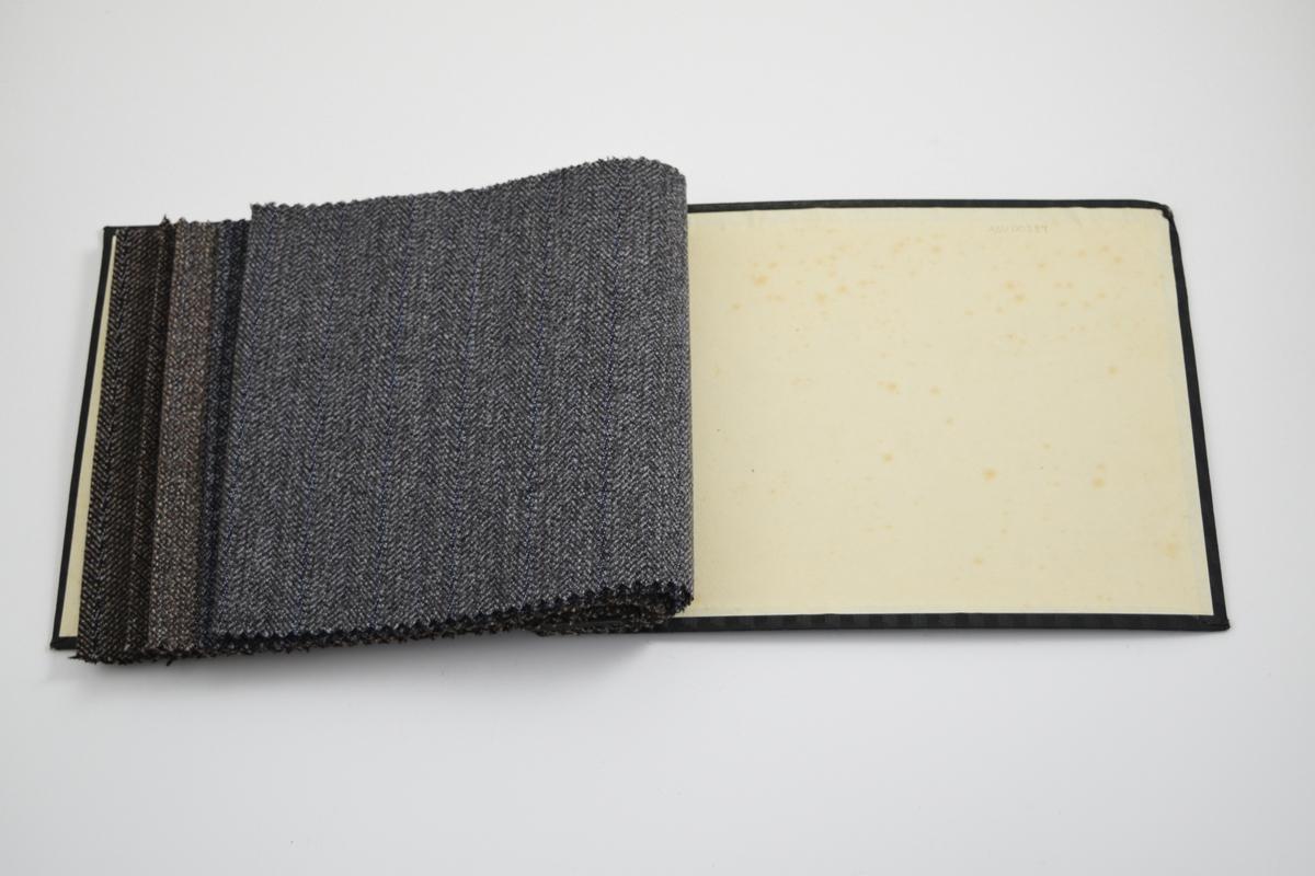 """Prøvebok med opprinnelig 7 prøver, to prøver er klippet ut så bare en liten bit er igjen i boken. Middels tykke stoff med ulike mønster. Ulikt vevemønster for alle prøvene, fargen varierer også. Stoffene ligger brettet dobbelt i boken. Stoffene er merket med en rund papirlapp, festet til stoffet med metallstifter, hvor nummer er påført for hånd. Påskriften på innsiden av forsideomslaget er antatt å angi kvaliteten """"Ryvingen"""" for alle stoffene i boken.  Stoff nr.: Ryvingen/101, Ryvingen/87 (antatt - prøven er klippet ut), Ryvingen/88, Ryvingen/89, Ryvingen/90, Ryvingen/91 (antatt - prøven er klippet ut), Ryvingen/92."""