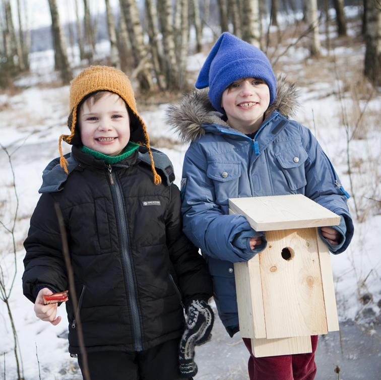 Foto av to gutter som holder en nysnekret fuglekasse