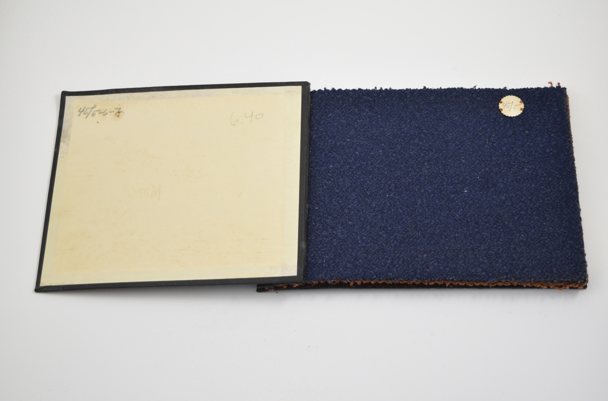 Prøvebok med 3 stoffprøver. Relativt tykke ensfargede stoff. Trådene stoffet er laget av har klumper slik at stoffet får en bølgede ujevn overflate - baksiden er imidlertid glatt. Stoffene ligger brettet dobbelt i boken slik at vranga dekkes. Stoffene er merket med en rund papirlapp, festet til stoffet med metallstifter, hvor nummer er påført for hånd.   Stoff nr.: Kv. 45/5, 45/6, 45/7.