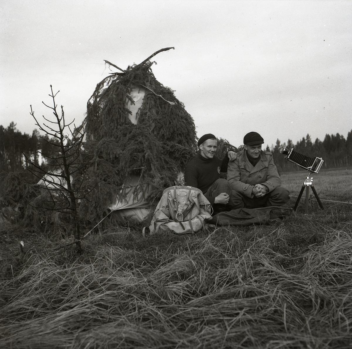 Två män sitter framför ett granristäckt tält och poserar. Hilding Mickelsson har kamratligt lagt sin arm på den andres axel medan de kikar mot fotografen. Bredvid männen står en kamera på stativ och en ryggsäck ligger lutad mot ena mannens ben. I förgrunden står ett barrlöst träd med grenar som sträcker sig över fjolårets grässtrån. Längs horisonten sticker skogens tallar upp och skärmar av himlavalvet från Degelmyren.