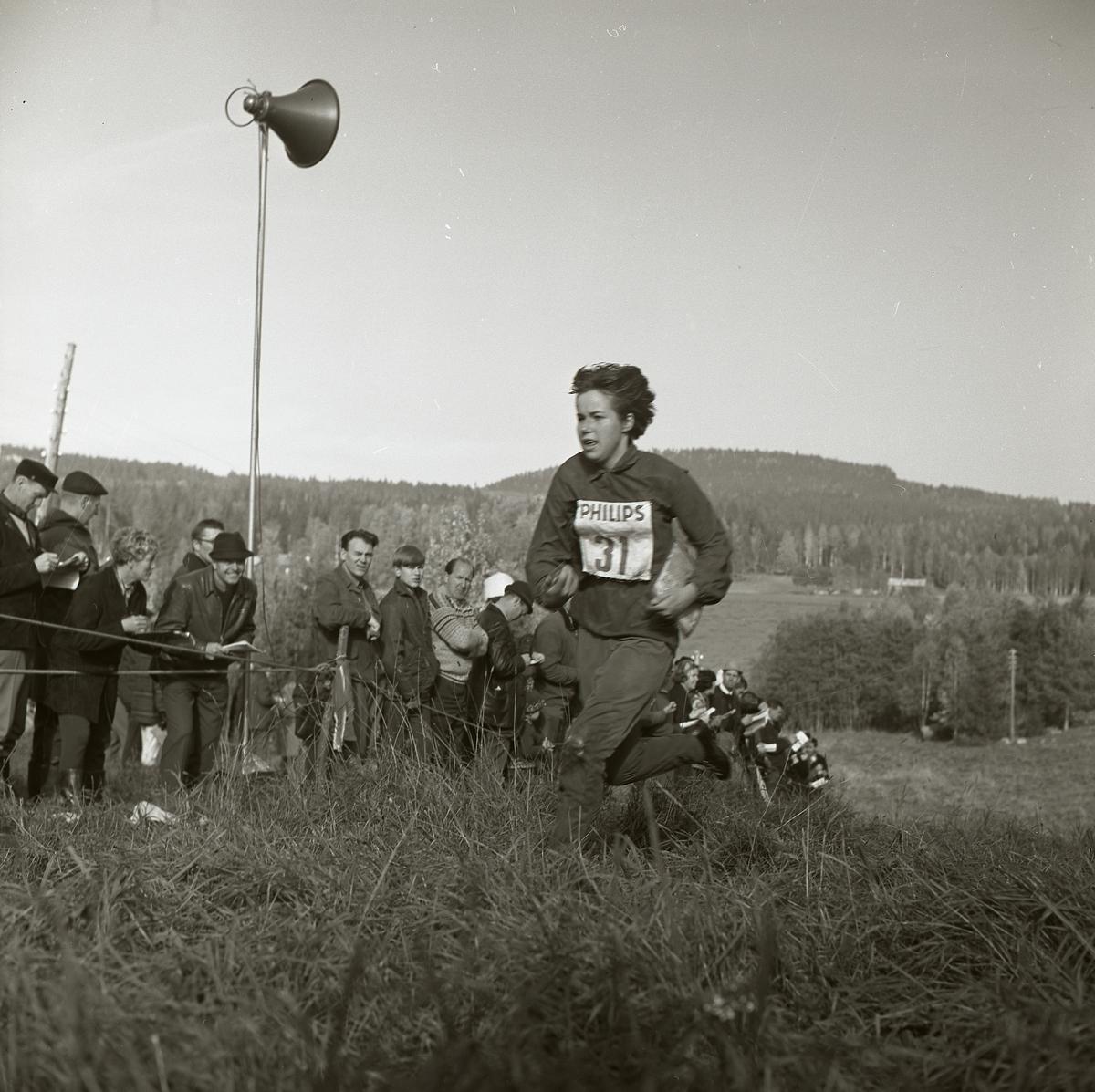 En kvinna springer iförd nummerlapp upp för en backe. Hon bär på en karta och är deltagare i svenska mästerskapen i orientering som hålls i Segersta 1965. Till vänster har en publik samlats bakom en avspärrning. På en stolpe sitter en högtalare som är placerad mitt i folkhopen.