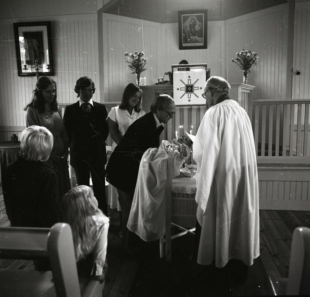 I kyrkans bänkrader sitter två barn och tittar omkring sig. De verkar måttligt intresserade av dopet som utspelar sig framför dem. Prästen iklädd vit kappa står framför bordet med vigvatten i en metallskål. En man sänker försiktigt ned barnen mot skålen för att döpas. Barnet bär en lång dopklänning och bakom dess huvud lyser två ljus. Två kvinnor och en man beskådar händelsen med glada miner.