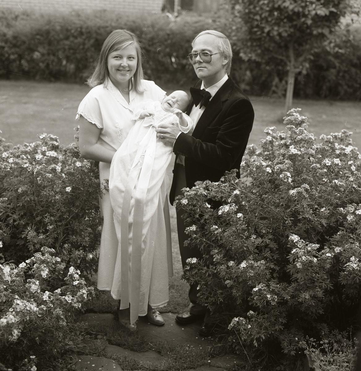 Med stolta uttryck visar föräldrarna upp sin nydöpta son, dagen till ära klädd i lång dopklänning. De poserar i en trädgård bland buskar med utslagna blommor, mannen klädd i kostym och kvinnan i klänning.