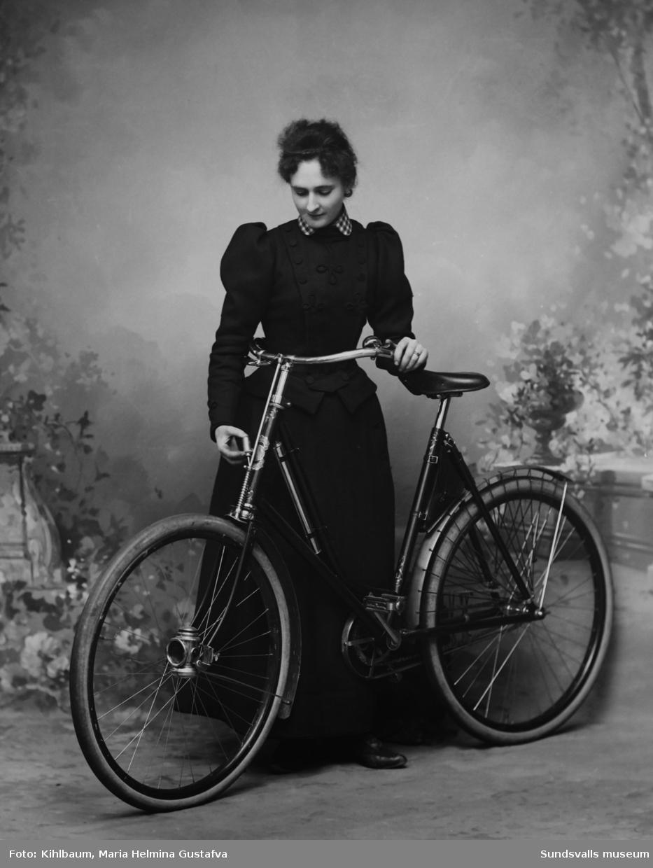 Porträtt av fotograf Maria Kihlbaum i hennes ateljé. Det ansågs djärvt och lite okvinnligt att cykla för en dam. Enligt uppgift så tillhörde Maria en av de första kvinnliga cyklisterna i Sundsvall. Bild 1 visar kopian och bild 2 glasnegativet.