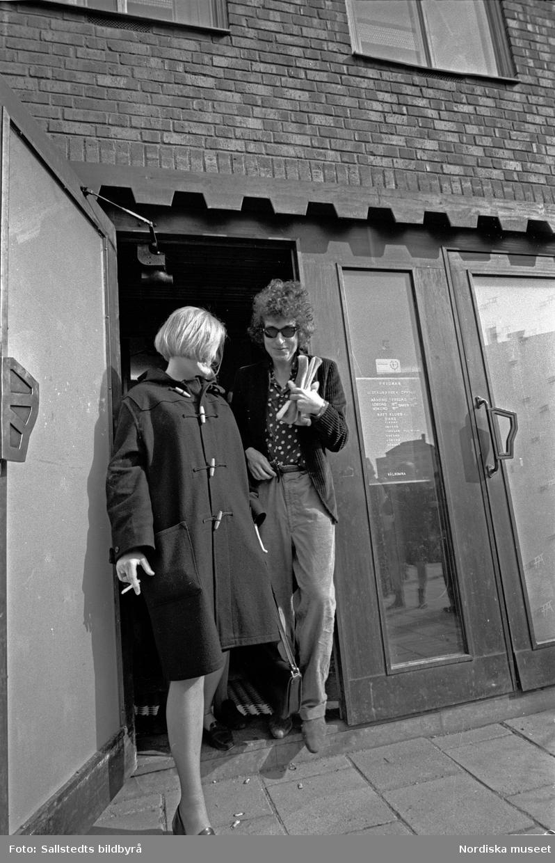 Artisten Bob Dylan lämnar Fredman Restaurang i Solna tillsammans med en kvinna under sverigebesöket 1966.