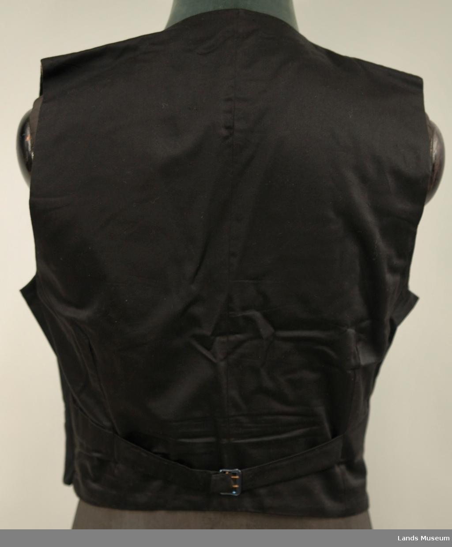 A: Jakke, Svart klede, krage med silkeslag. Enkeltspent, 1 trekt knapp, 3 trekte knapper på kvar arm. Svart silkefor. L.71,5 cm bredde ved skuldrane 45 cm B: Bukse, svart klede, silkeripsbånd i sidene. L. 103 cm, Vidde nede 24 cm C: Vest, svart klede, svart silkefor i rygg, foret med lystripet sateng. Enkeltspent med 4 trekte knapper, 4 lommer. L.48,5 cm x 38 cm D: Sløyfe, Sort silkerips 55cm x 3,5 cm