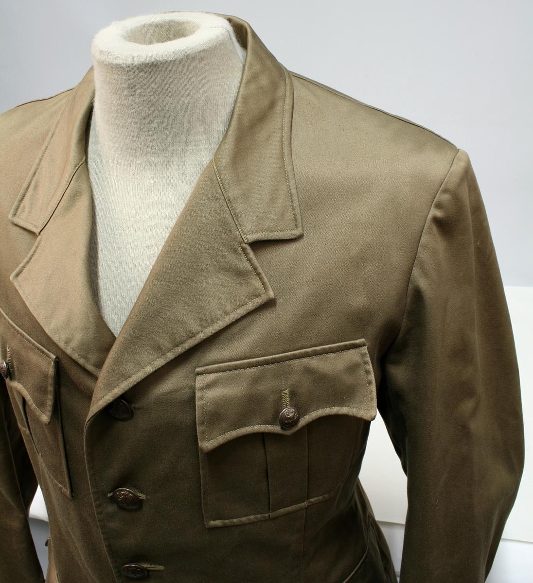 Nokså lik 1953 modellen. Enkeltkneppet brun jakke med fire knapper, fire ytterlommer og nedbrettet krage.