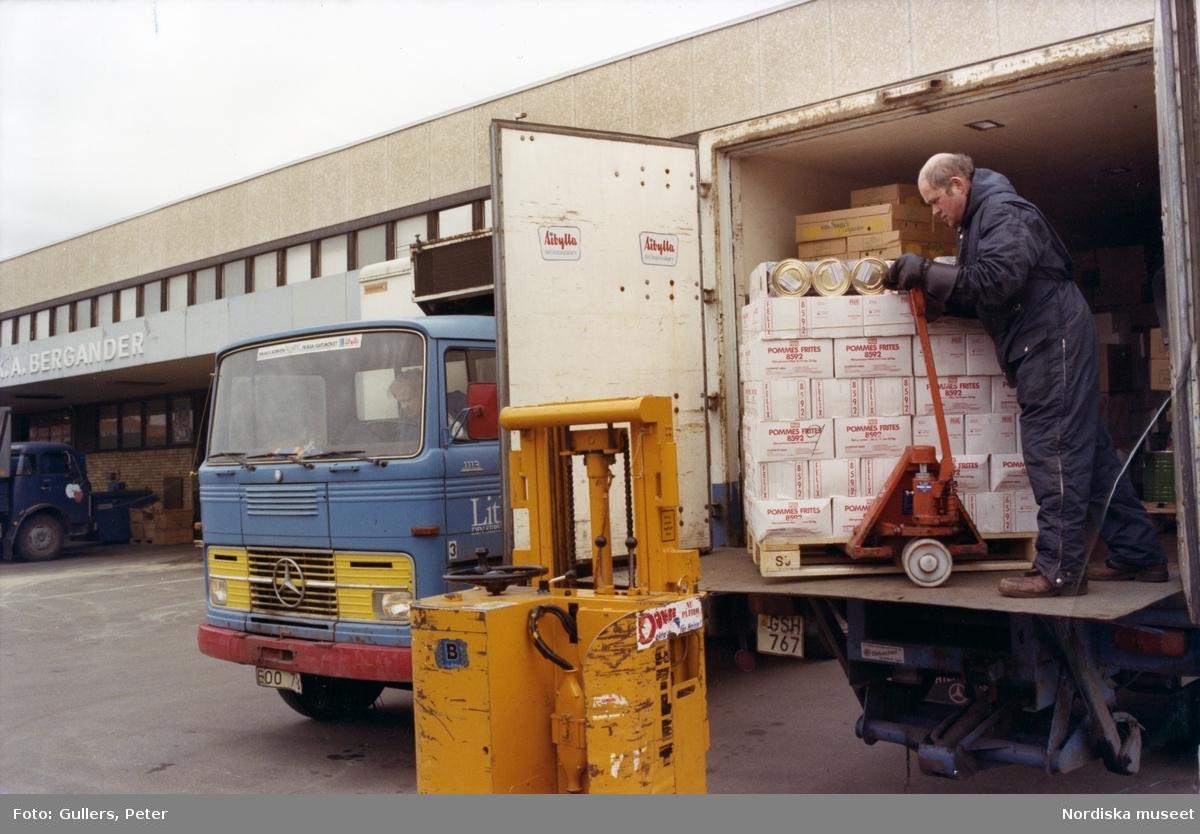 En man lastar en lastbil vid Årsta partihallar, Stockholm. Mannen använder en handtruck, på marken framför lastbilen står en eltruck. I bakgrunden företaget K A Berganders byggnad.