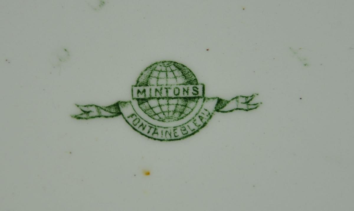 Rund tallerken av keramikk, steingods, med grønn bord. Borden består av eikekrans og guirlandere. Mønsteret heter Fontainebleau.