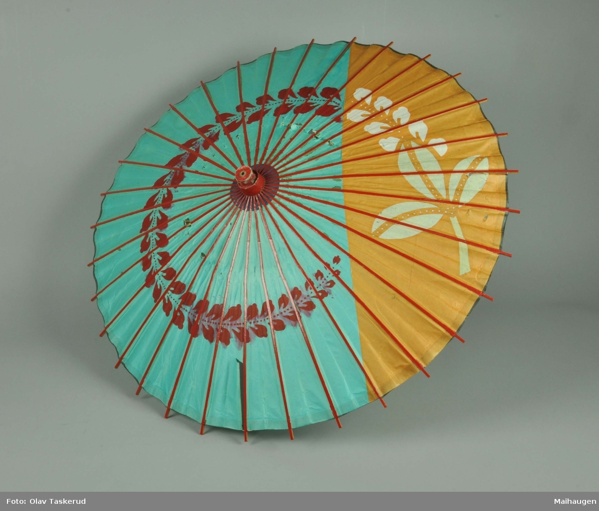 Parasoll av trespiler trukket med papir innvendig. papiret har trykte blomstermotiv. Utvendig er parasollen rødmalt.