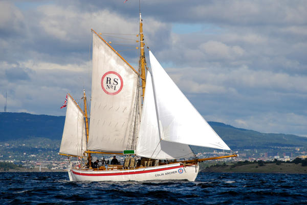 RS1 Colin Archer på vannet med tre seil, land i bakgrunnen.. Foto/Photo