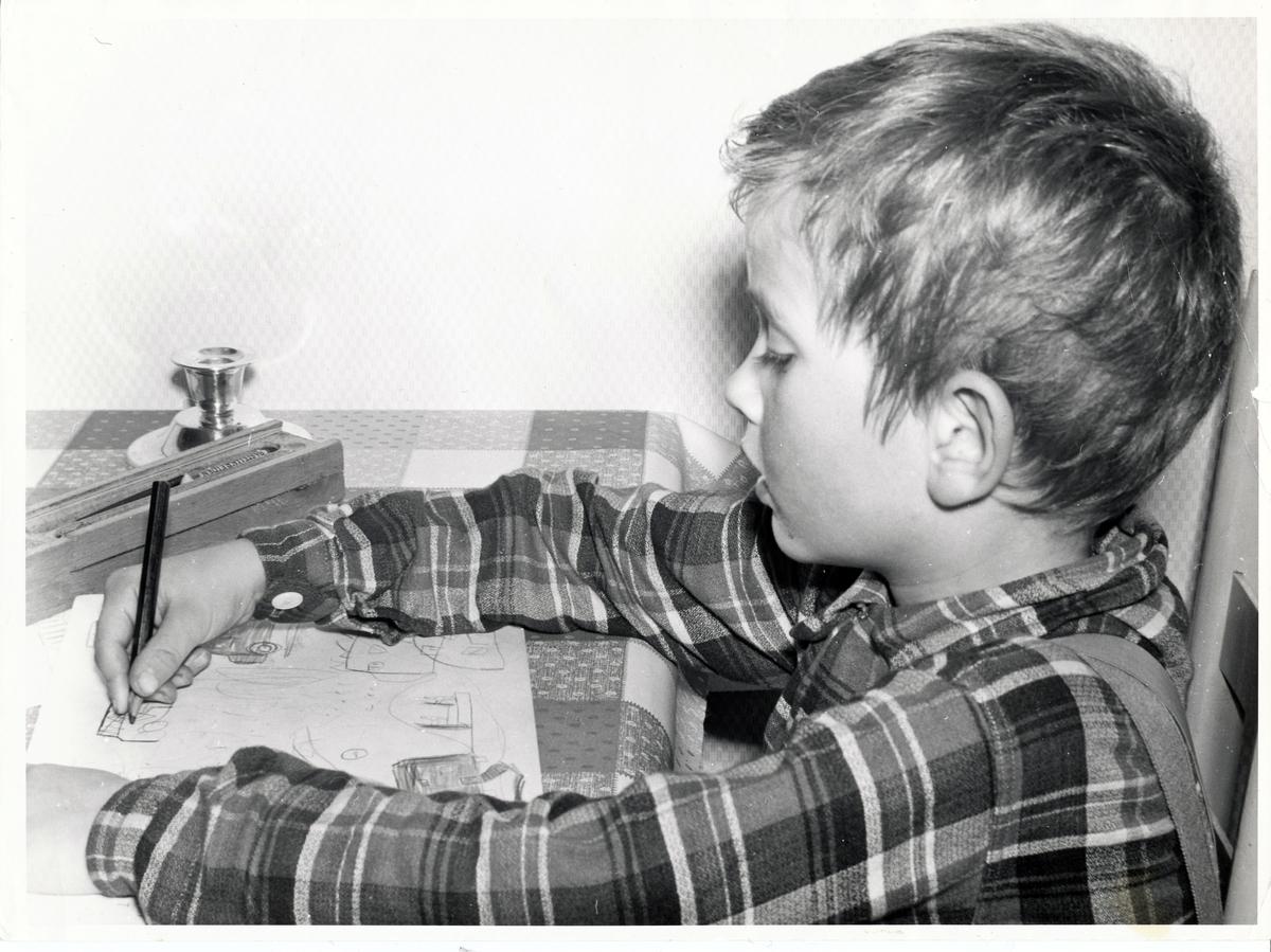 En liten gutt som tegner.