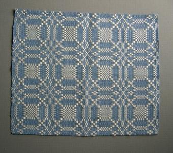 Vävprov i bomull och lin vävt i daldräll. Gallermönster i vitt med cirklar och kvadrater på blå botten.Varp och botteninslag i blått bomullsgarn. Mönsterinslag i blekt lingarn.