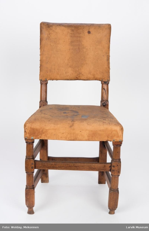 Form: rett,avskåret, rekt. rygg, bakstolper i ett med Uten armlener Firesidige bakben, høvlet sprosseverk, festet med trenagler,skinntrekk på sete og rygg,festet med messingstifter