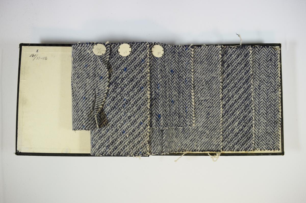 Prøvebok med 6 stoffprøver. Middels tykke stoff med skrå striper eller fiskebensmønster. Alle stoffene er merket med en rund papirlapp, festet til stoffet med metallstift, hvor nummer er påført for hånd. Innskriften på innsiden av forsideomslaget indikerer at all stoffene har kvalitetsnummer 161.   Stoff nr.: 161/37, 161/38, 161/39, 161/40, 161/41, 161/42.