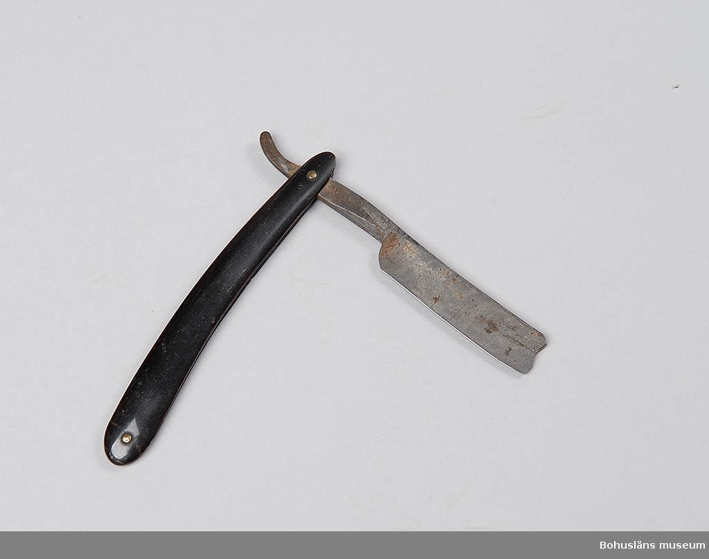 Funktion: för rakning. Hopfällbar rakkniv mes skaft av svart horn och slipad kniv av stål. Eskilstunatillverkning?