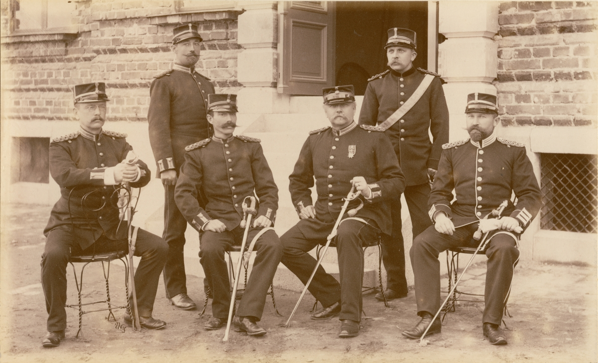Sex officerare från Andra livgrenadjärregementet I 5 sitter utanför kasernbyggnad.