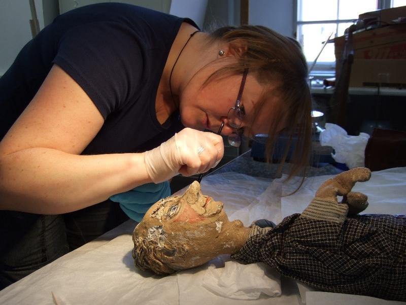Gjenstandskonservator Helga Marie Stangeby renser ansiktet til en teaterdukke fra Asker museums samling. Foto: MiA (Foto/Photo)