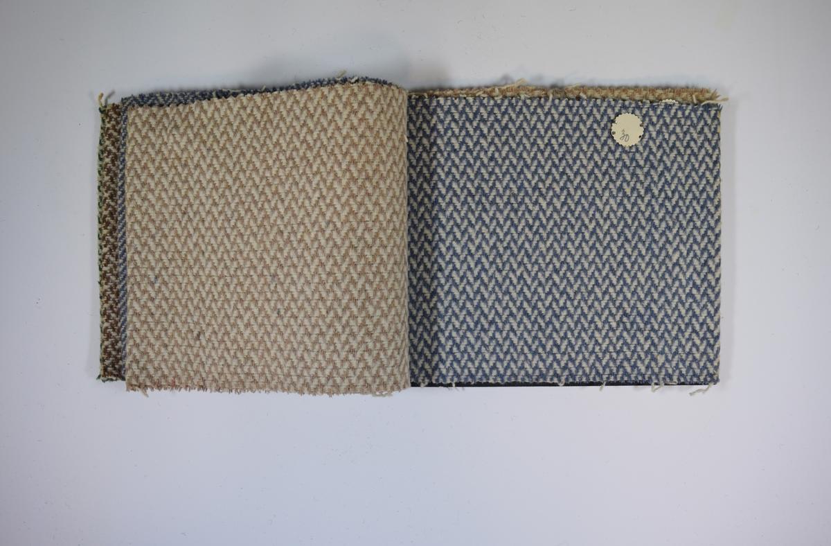 Prøvehefte med 6 prøver. Middels tykke stoff med fire ulike mønstere. Ulike farger på stoffene, men alle i kombinasjon med hvitt. Tovet overflate. Baksiden er ikke tovet. Stoffene ligger brettet dobbelt i heftet. Stoffene er merket med en rund papirlapp, festet til stoffet med metallstifter, hvor nummer er påført for hånd. Heftet har stiv bakplate og en papp-plate der heftet er stiftet som dekker ca. 5 cm forsiden. På pappen på forsiden er det en innskrift som indikerer at alle stoffene har kvaliteten 162.   Stoff nr.: 162/7, 162/11, 162/13, 162/29, 162/30, 162/36.