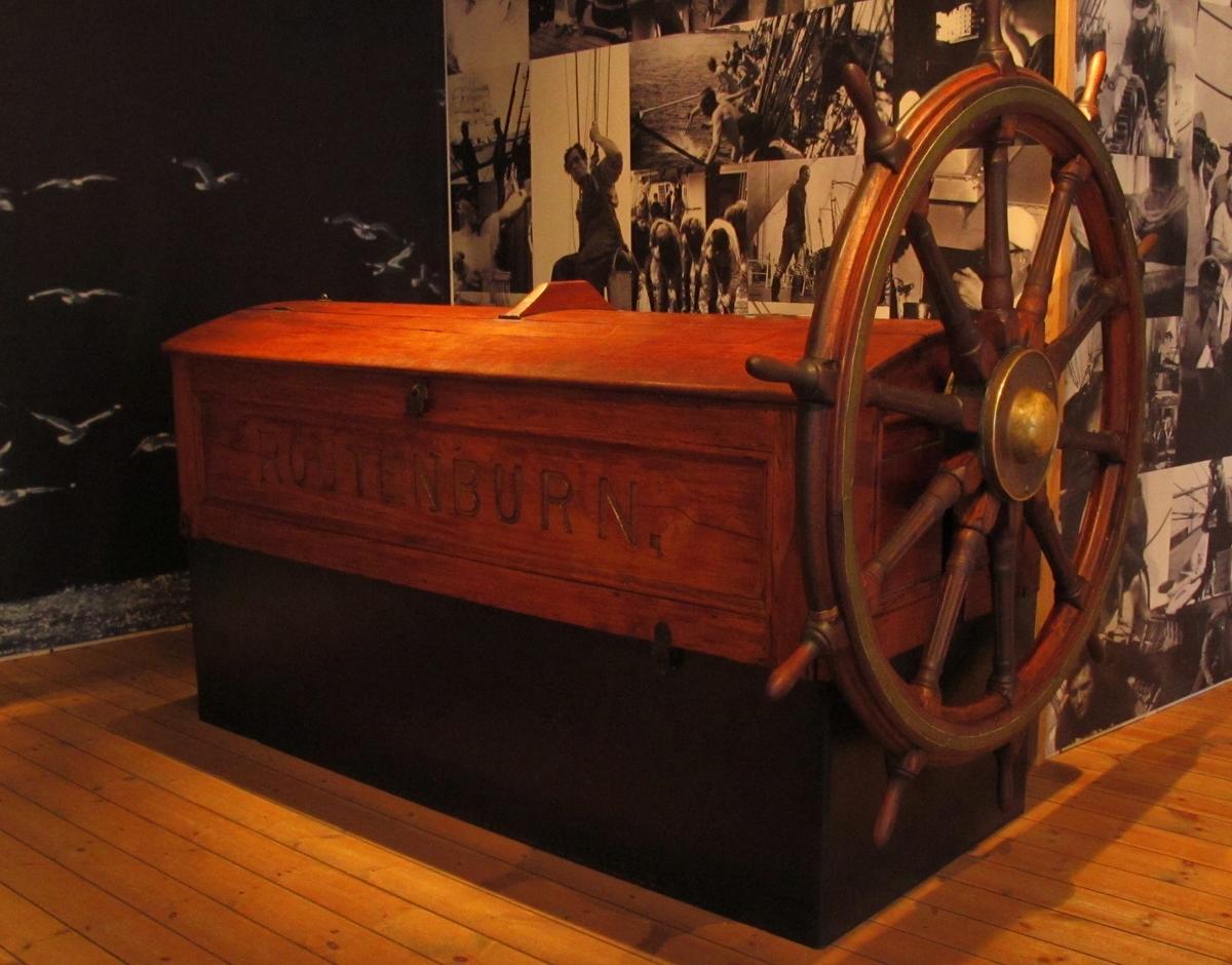 """Roderkista från 4-mastade barken BEATRICE, byggd 1881 som ROUTENBURN. Av teak med två lock. På ömse sidor namnet """"ROUTENBURN"""", men på styrbord sida är texten översatt med namnbräda med namnet BEATRICE (S 1966.2) , som barken hette från 1922.  Vid roderkistan är en ratt fäst. På ratten namnet SVITHIOD, som barken hette 1905-1922."""