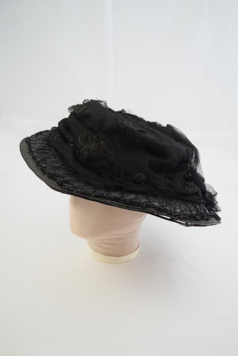 """Stråhatt med bred brem. Bremmen prydet med et bånd av strå med 3 og 3 blader i grupper. Pullen er dekket av sort chiffon og tyll med mønster av blader og strå. Sort spenne på bremmen i høyre side, 2,6 cm På bremmens underside trekk av sort mønstret bobinett. Over pannen en 21 cm lang, smal """"skjerm"""" av fløyel pyntet med sorte silkeblomster. Hatten er foret med sort bomullsstoff."""