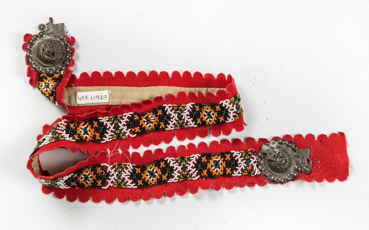 Belte, perlesteinbelte tredd i svarte, kvite, grønne og gule perler. Bunn av rødt klede. Langsidene har utstansa, tagga halvsirkler ca 1 cm i diameter. Sylvspenne med eit hengekors i kvar ende. Fòra på baksida med ubleikt bomullstøy.
