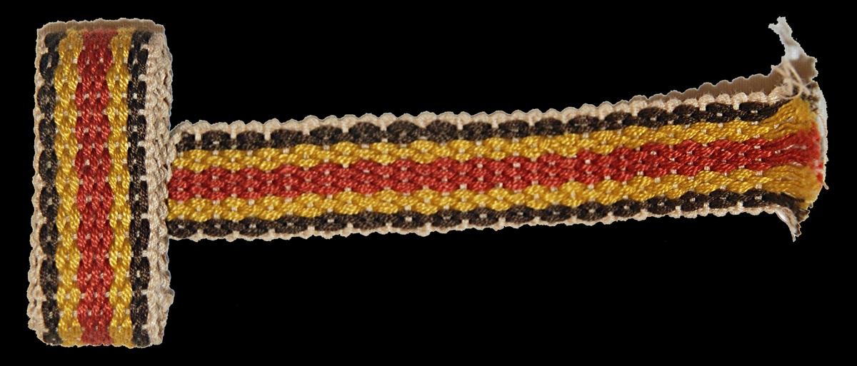 Band 49 x 2 cm. Merceriserad bomull, ripsvävt. Randigt i brunt, gult och rött.  Katalogiserad av Karin Nordenfelt, Elisabet Stavenow, Marie-Louise Wulfcrona-Dagel.