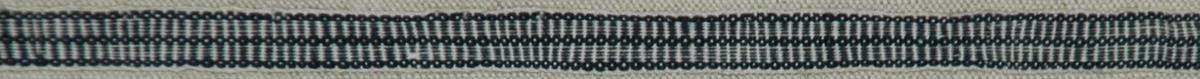 Band 85 x 1 cm. Bomull, ripsvävt, mönstrat i vitt och mörkblått.  Katalogiserad av Karin Nordenfelt, Elisabet Stavenow, Marie-Louise Wulfcrona-Dagel.