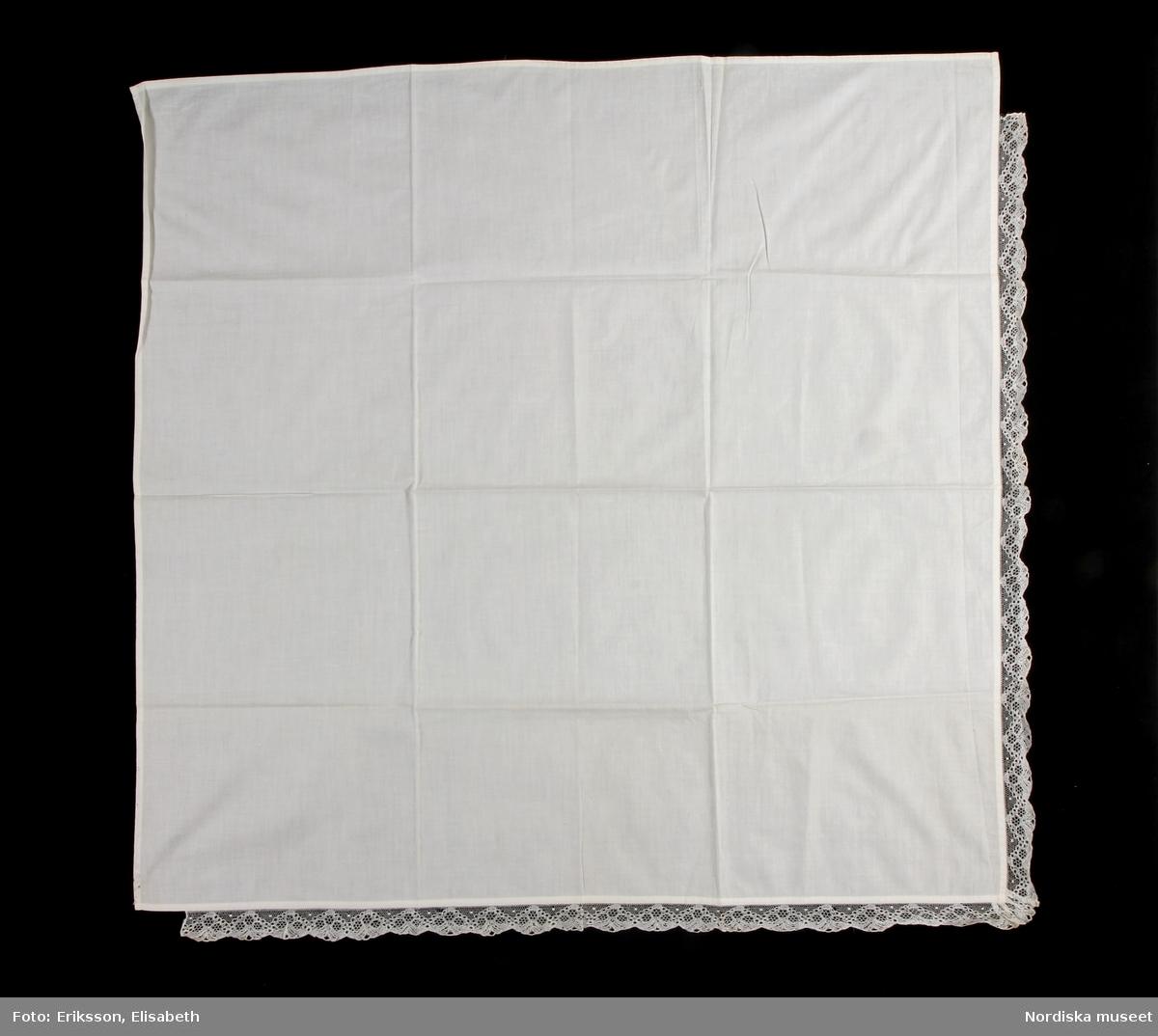 Kvadratiskt kläde av tunn vit bomullslärft, handsydda fållar runtom. I 2 mötande sidor kantad med 3 cm bred knypplad Vadstenaspets.  Se likadant kläde inv.nr 1105. /Berit Eldvik 2010-08-31