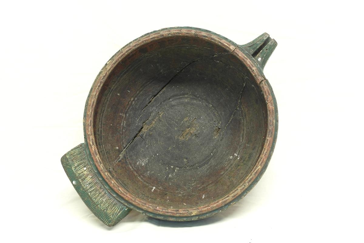 Tutskål/Kjenge i dreiet, skåret, pusset og malt furu. Skålen har tut ved kanten og et håndtak på motsatt side. På utsiden langs kanten er det skåret en bord i karveskurd. Det er skåret dekor på håndtak og tut. I bunnen er det skåret en rose. Innvendig er det rester av maling øverst, og lenger ned rester av gult og svart. På utsiden er skålen grønnmalt langs den skårne kanten, og resten er malt i flammebjerksimitasjon.