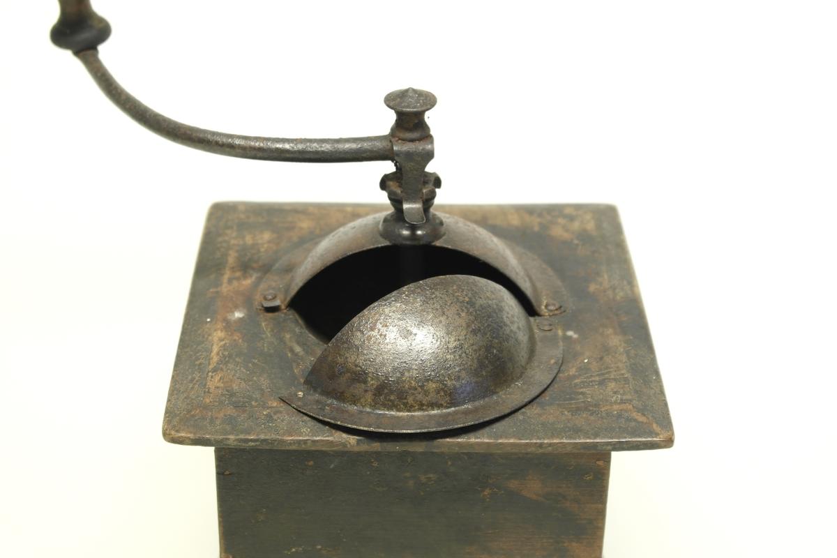 Kaffekvern (a og b) i tre, jern og messing.  a) Kvadratisk kasse med topplate og bunnplate. Sveiv som går ned til innsatt tannhjul, som kverner kaffebønnene. Klokkeformet deksel som kan åpnes med en klaff som skyves til siden. Messingskilt med stempel. b) Skuff som samler opp den malte kaffen. Stiftet i hjørner og bunnplate.